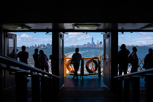 Silhouettes of passengers traveling from New York City aboard the Staten Island Ferry. The Manhattan skyline is seen through the windows in the distance.