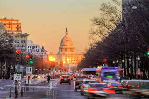 US Capitol Building with Pennsylvania Ave at dusk.