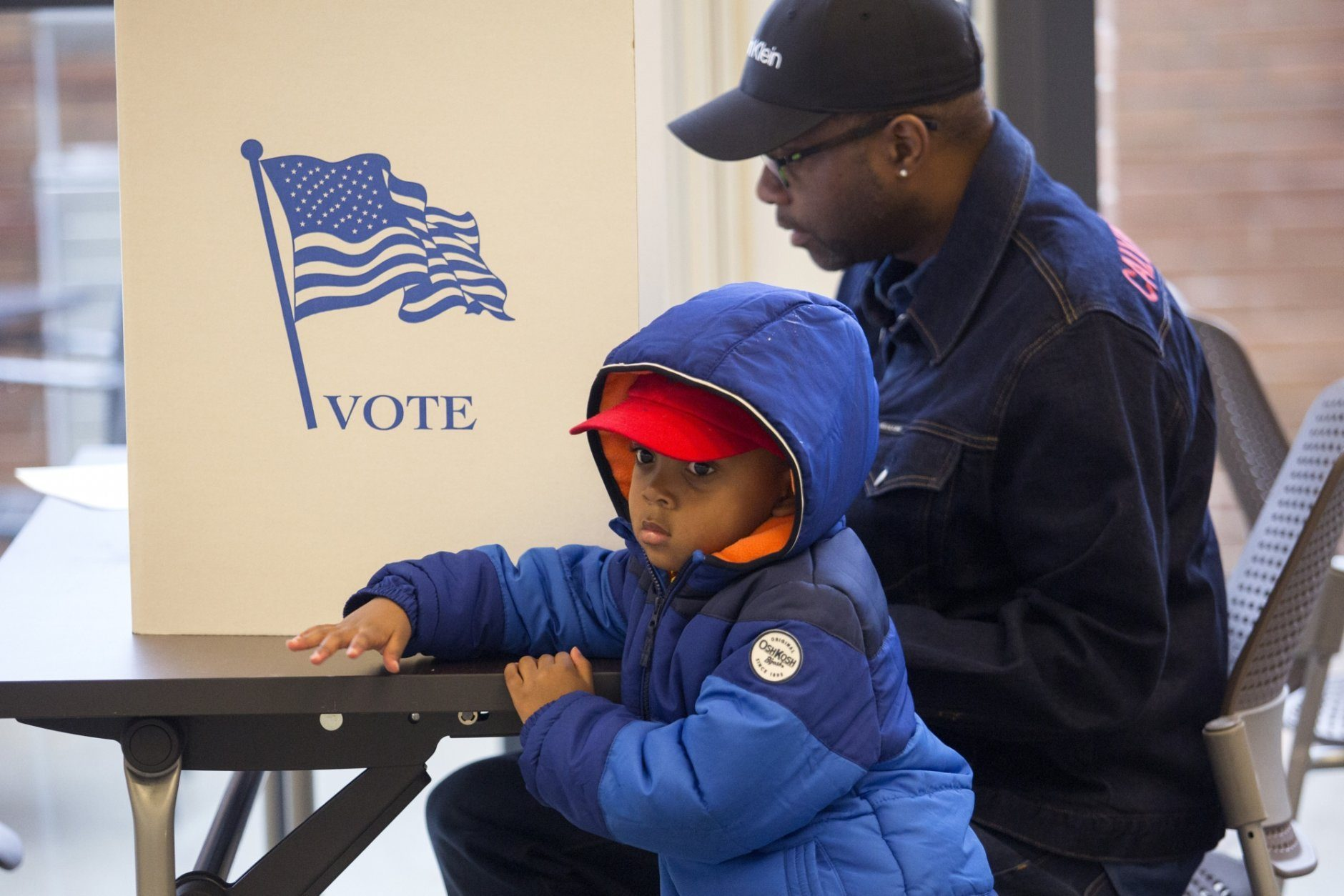 Asher Artis, 3, waits for his grandfather, Keith Smith, to finish filling out his ballot at The Kroc Center Hampton Roads, a polling location in Norfolk, Va., on Tuesday, Nov. 5, 2019.  (Sarah Holm/The Virginian-Pilot via AP)
