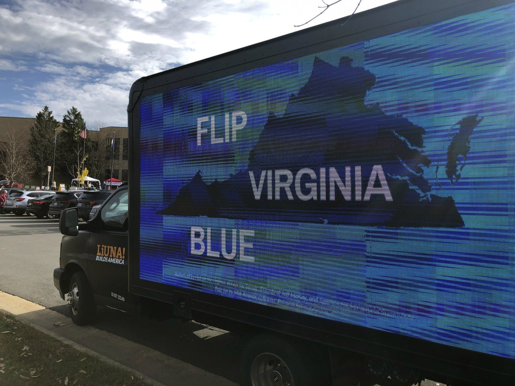 A mobile billboard urges voters to cast ballots for Democrats outside Centreville High School in Clifton, Va., Tuesday, Nov. 5, 2019. (AP Photo/Matthew Barakat)