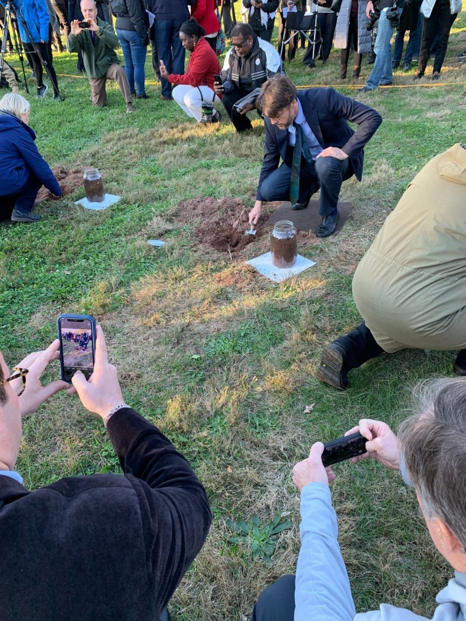 Community members took turns collecting dirt from the spot where George Peck was lynched in 1880.