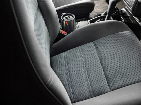Tight shot of a car interior main focus on the car's gray cloth bucket seat.