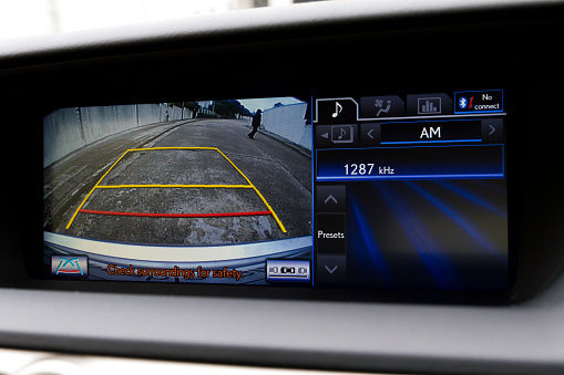 A stock photo of an in dash reversing camera showing the view of a suburban driveway.