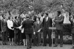 U.S.President Ronald Reagan shakes hands with Patrick Ewing, left, and Michael Graham, right, as Georgetown University academic coordinator Mary Fenlon looks on, during a ceremony for the Georgetown University NCAA Champion basketball team, in the Rose Garden of the White House, Saturday, April 7, 1984 in Washington. (AP Photo/Charles Tasnadi)