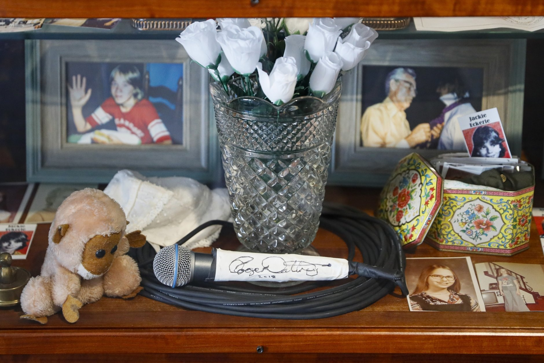 In this Thursday, Nov. 21, 2019 photo, a signed microphone by The Who's Roger Daltrey is displayed in a memorial cabinet at the Finneytown High School secondary campus in Finneytown, Ohio, along with other mementoes of the three Finneytown students killed in a stampede at the band's 1979 Cincinnati concert. Tragedy four decades ago linked the British rock band to the small suburban city in Ohio. In recent years, members of the community and the band have bonded through a project to memorialize the teens. (AP Photo/John Minchillo)