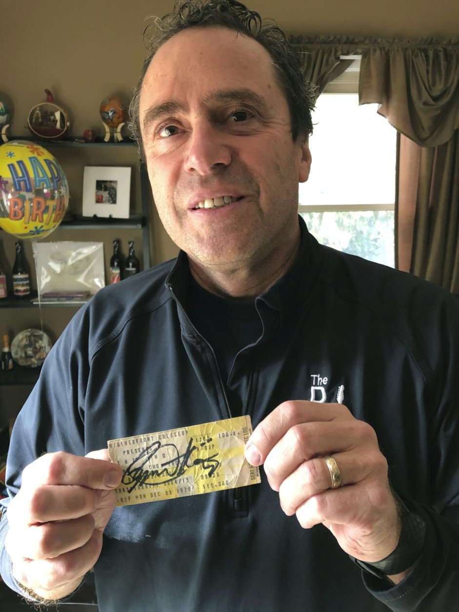 In this Nov. 25, 2019 photo, Finneytown High School alumnus John Hutchins displays a Dec. 3, 1979, concert ticket signed in 2018 by The Who's vocalist Roger Daltrey as he stands in his home near Finneytown, Ohio. Hutchins helped organize a memorial scholarship fund to honor three Finneytown students killed in a fan stampede at The Who's Cincinnati concert 40 years ago. (AP Photo/Dan Sewell)