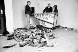 FILE - In this Dec. 3, 1979 file photo, concert-goers and a policeman stand with a pile of shoes and clothing which were left after a crowd surged toward doors to Cincinnati's riverfront coliseum to get into a rock concert by British rock band The Who, in Cincinnati, Ohio. Eleven fans where killed in the tragedy. (AP Photo/Brian Horton, File)