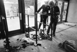 FILE - In this Dec. 3, 1979 file photo, a security guard and an unidentified man look at an area where several people were killed as they were caught in a surging crowd entering Cincinnati's riverfront coliseum for a concert by the British rock band The Who. (AP Photo/Brian Horton, File)