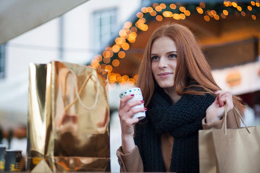 Young female shopper with shopping bags, smiling and drinking mulled wine in city center with christmas lights. Christmas market scene.