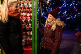 Two women shopping for Christmas ornaments at night in New York City.
