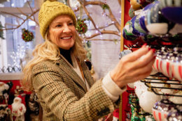 A side view shot of a mature woman wearing warm clothing christmas shopping on a cold evening in New York City, she can be seen looking at christmas decorations with a smile on her face.