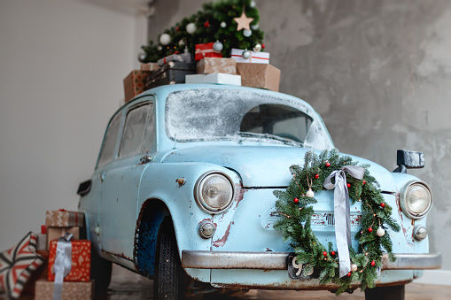 Blue retro car carrying the giftboxes and xmas tree