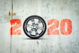 2020. The inscription on the concrete wall. Auto wheel instead of zero. Christmas background. Greeting card for a car workshop. Auto mechanics.