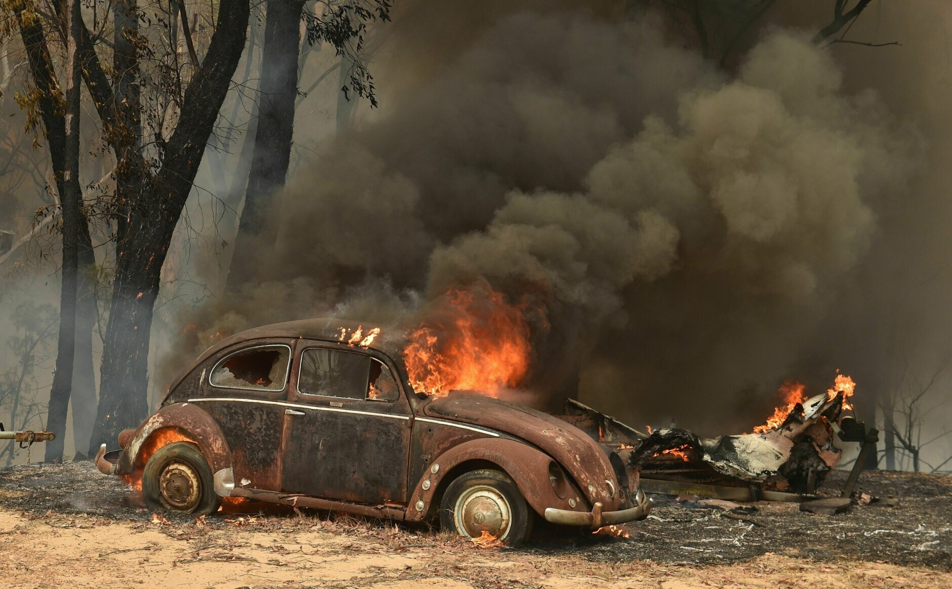 TOPSHOT - An old car burns from bushfires in Balmoral, 150 kilometres southwest of Sydney on December 19, 2019. - A state of emergency was declared in Australia's most populated region on December 19, as a record heat wave fanned unprecedented bushfires. (Photo by PETER PARKS / AFP) (Photo by PETER PARKS/AFP via Getty Images)