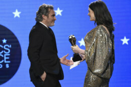 "Anne Hathaway, right, presents the award for best actor to Joaquin Phoenix for ""Joker"" at the 25th annual Critics' Choice Awards on Sunday, Jan. 12, 2020, at the Barker Hangar in Santa Monica, Calif. (AP Photo/Chris Pizzello)"