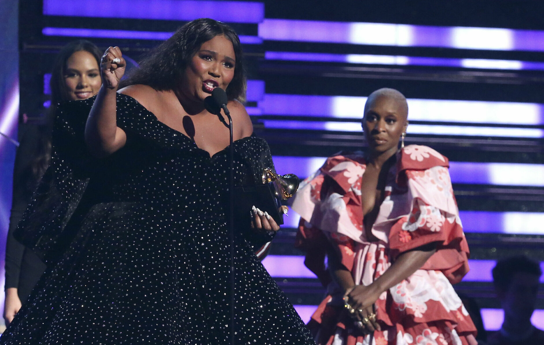"Lizzo accepts the award for best pop solo performance for ""Truth Hurts"" at the 62nd annual Grammy Awards on Sunday, Jan. 26, 2020, in Los Angeles. Looking on at right is Cynthia Erivo. (Photo by Matt Sayles/Invision/AP)"