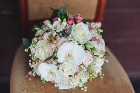 Wedding bouquet on a vintage chair. Orchid, rose.