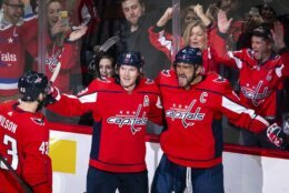 Washington Capitals left wing Alex Ovechkin (8), from Russia, celebrates after scoring as right wing Tom Wilson (43), from Canada, and Nicklas Backstrom (19), from Sweden, join during the first period of an NHL hockey game against the Carolina Hurricanes, Monday, Jan. 13, 2020, in Washington. (AP Photo/Al Drago)