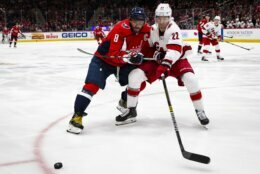 Washington Capitals left wing Alex Ovechkin (8), from Russia, and Carolina Hurricanes defenseman Brett Pesce (22) reach for the puck during the second period of an NHL hockey game, on Monday, Jan. 13, 2020, in Washington. (AP Photo/Al Drago)