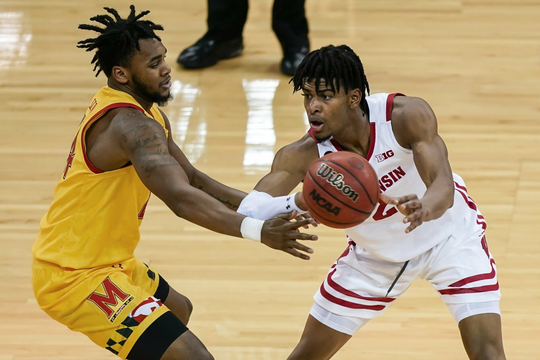 Wisconsin's Aleem Ford (2) passes the ball as Maryland's Donta Scott defends during the first half of an NCAA college basketball game Tuesday, Jan. 14, 2020, in Madison, Wis. (AP Photo/Andy Manis)