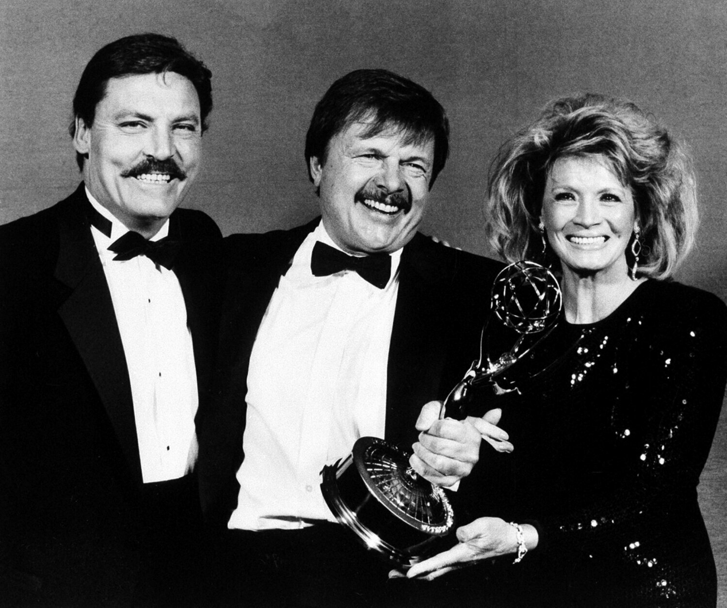 """FILE - This Sept. 21, 1986 file photo shows actor John Karlen, center, who portrays the husband of detective Mary Beth Lacey on the TV show """"Cagney & Lacey, """" posing with presenters Stacy Keach, left, and Angie Dickinson after Karlen won an Emmy for best supporting actor at the Emmy Awards in Pasadena, Calif.  Karlen, known for his roles on the television series """"Dark Shadows"""" and """"Cagney & Lacey,"""" died Wednesday, Jan. 22, 2020, of congestive heart failure in Burbank, Calif. He was 86. (AP Photo/Douglas C. Pizac, File)"""