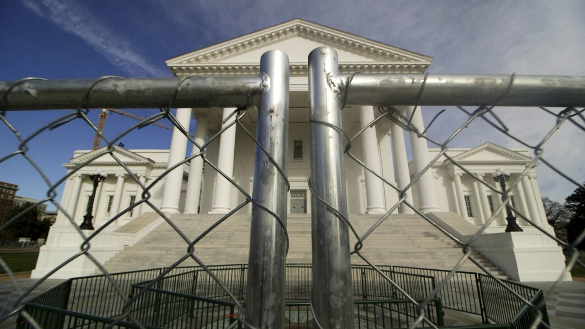 The Virginia state Capitol building is surrounded by fencing, Thursday, Jan. 16, 2020 in Richmond, Va., in preparation for Monday's rally by gun rights advocates. Gun-rights groups are asking a judge to block the Virginia governor's ban on firearms at a massive pro-gun rally scheduled for next week. Gov. Ralph Northam on Wednesday, Jan. 15, announced a state of emergency and banned all weapons from the rally at the Capitol.  (Dean Hoffmeyer/Richmond Times-Dispatch via AP)