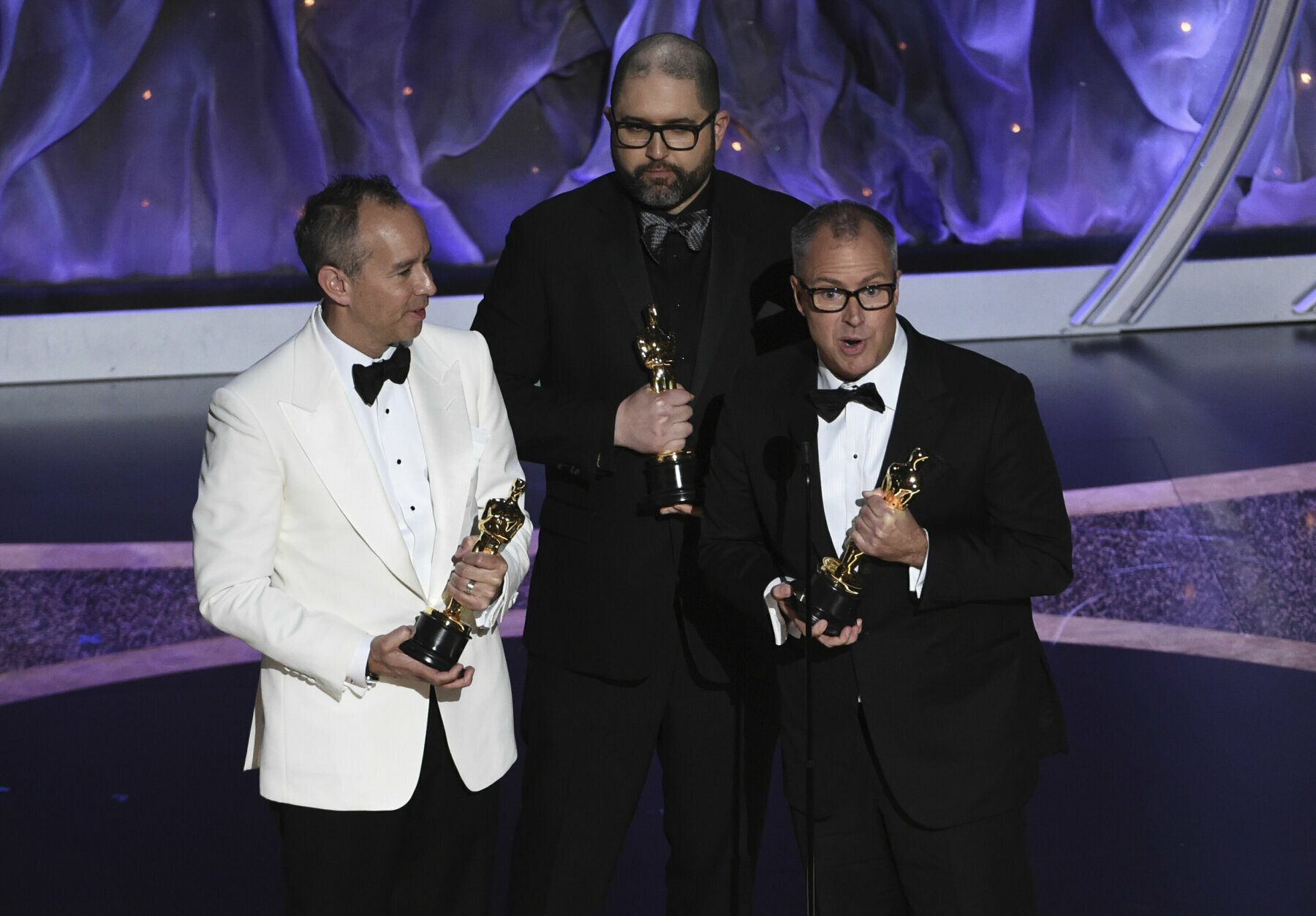 """Jonas Rivera, from left, Josh Cooley and Mark Nielsen accept the award for best animated feature film for """"Toy Story 4"""" at the Oscars on Sunday, Feb. 9, 2020, at the Dolby Theatre in Los Angeles. (AP Photo/Chris Pizzello)"""
