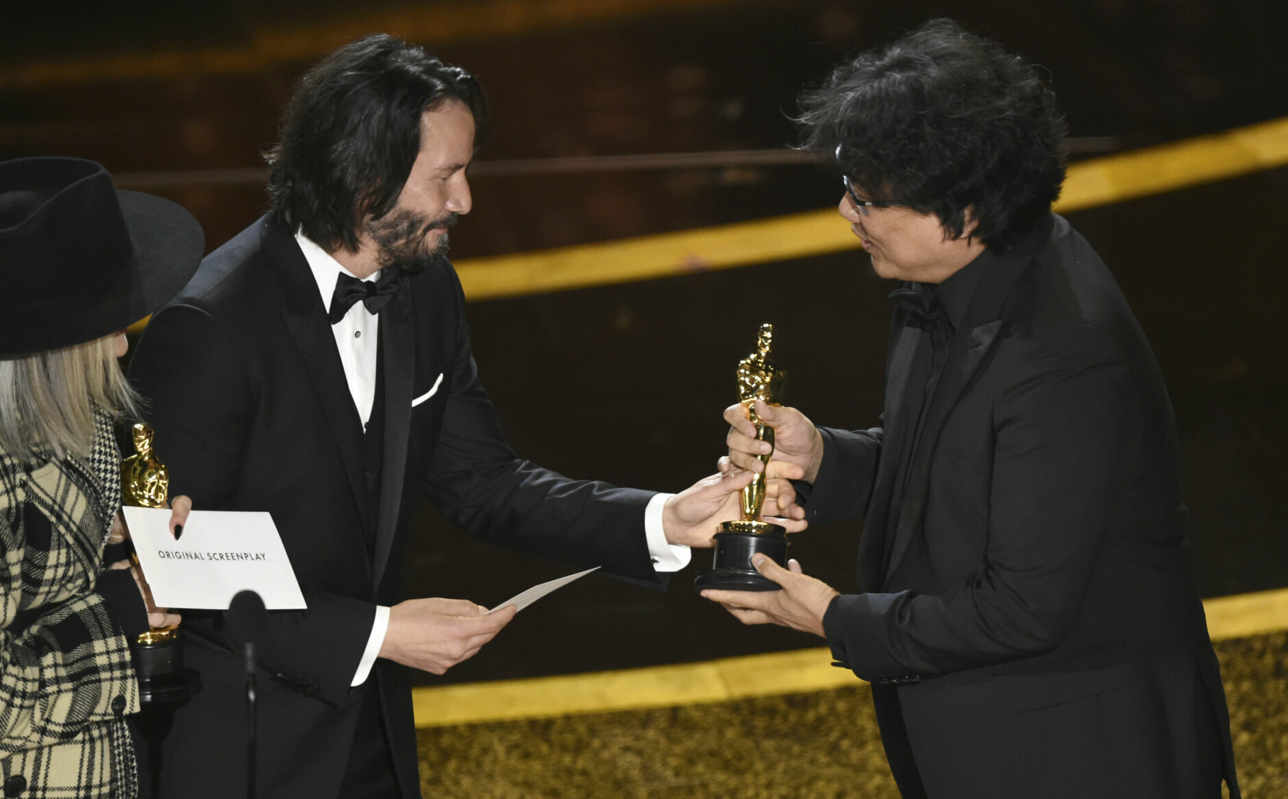 """Diane Keaton, from left, and Keanu Reeves present the award for best original screenplay to Bong Joon Ho for """"Parasite"""" at the Oscars on Sunday, Feb. 9, 2020, at the Dolby Theatre in Los Angeles. (AP Photo/Chris Pizzello)"""