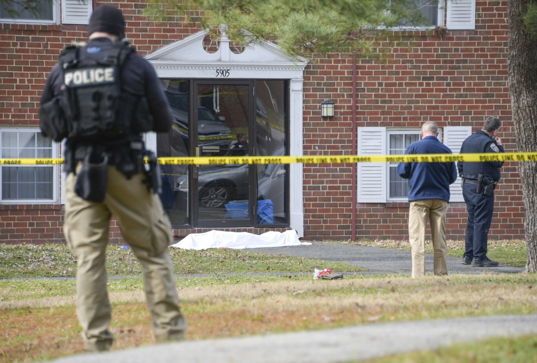 Law enforcement personnel work at the scene which appears to show a body covered under a white blanket outside of an apartment, Wednesday, Feb. 12, 2020, in Baltimore. Two law enforcement officers with a fugitive task force were injured and a suspect died in the shooting, the U.S. Marshals Service said. (Ulysses Muñoz/The Baltimore Sun via AP)