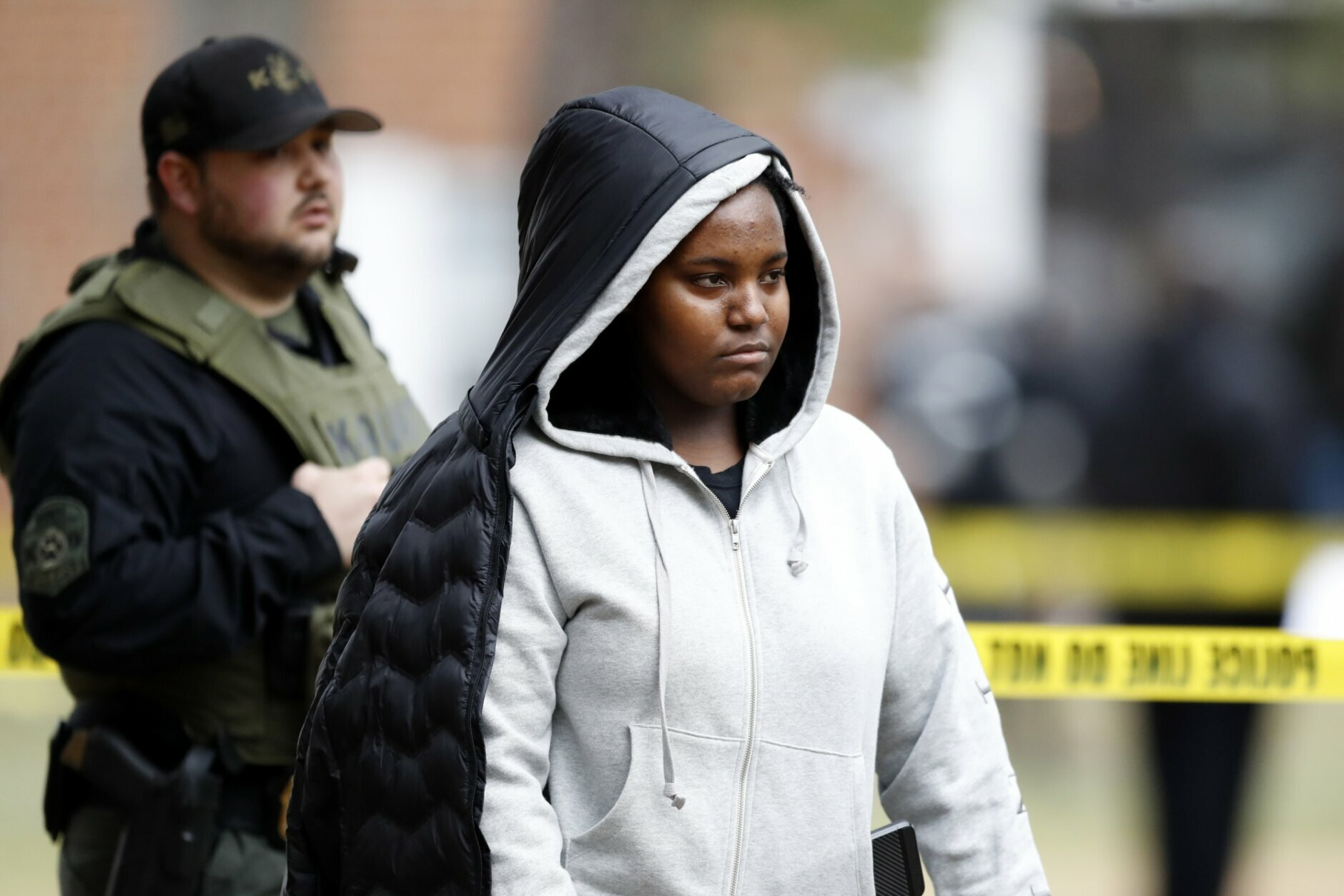A person reacts while talking to security officers at an apartment complex near the scene of a shooting, Wednesday, Feb. 12, 2020, in Baltimore. Two law enforcement officers with a fugitive task force were injured and a suspect died in the shooting, the U.S. Marshals Service said. (AP Photo/Julio Cortez)