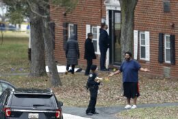 A person reacts while talking to an official at an apartment complex near the scene of a shooting, Wednesday, Feb. 12, 2020, in Baltimore. Two law enforcement officers with a fugitive task force were injured and a suspect died in the shooting, the U.S. Marshals Service said. (AP Photo/Julio Cortez)