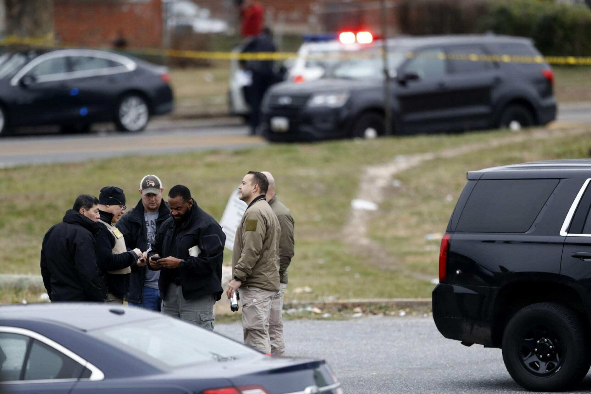 Investigators work the scene of a shooting, Wednesday, Feb. 12, 2020, in Baltimore. Two law enforcement officers with a fugitive task force were injured and a suspect died in the shooting, the U.S. Marshals Service said. (AP Photo/Julio Cortez)