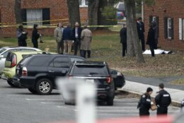 A sheet is seen over a suspect's body outside an apartment complex as investigators work the scene of a shooting, Wednesday, Feb. 12, 2020, in Baltimore. Two law enforcement officers with a fugitive task force were injured and a suspect died in the shooting, the U.S. Marshals Service said. (AP Photo/Julio Cortez)