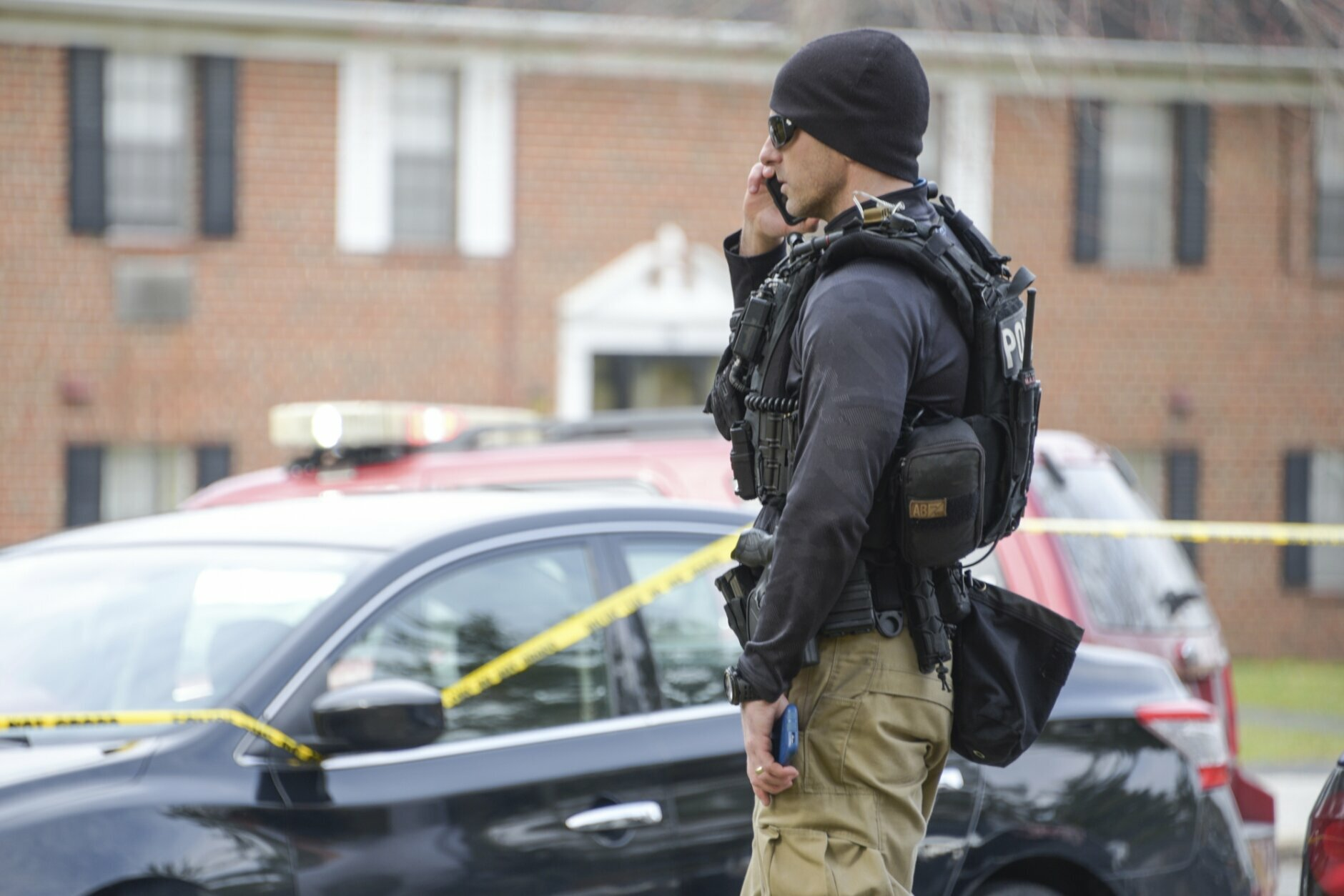 Law enforcement personnel work at the scene of a shooting, Wednesday, Feb. 12, 2020, in Baltimore. Two law enforcement officers with a fugitive task force were injured and a suspect died in the shooting, the U.S. Marshals Service said. (Ulysses Muñoz/The Baltimore Sun via AP)