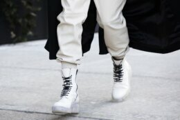 A model walks in laced white boots while arriving for a show during Fashion Week, Wednesday, Feb. 12, 2020 in New York. (AP Photo/Mark Lennihan)