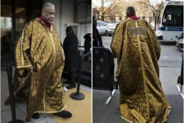 """Fashion journalist Andre Leon Talley walks outside a show during Fashion Week, Wednesday, Feb. 12, 2020, in New York. He wears a cape with the name """"Dapper Dan."""" (AP Photo/Mark Lennihan)"""
