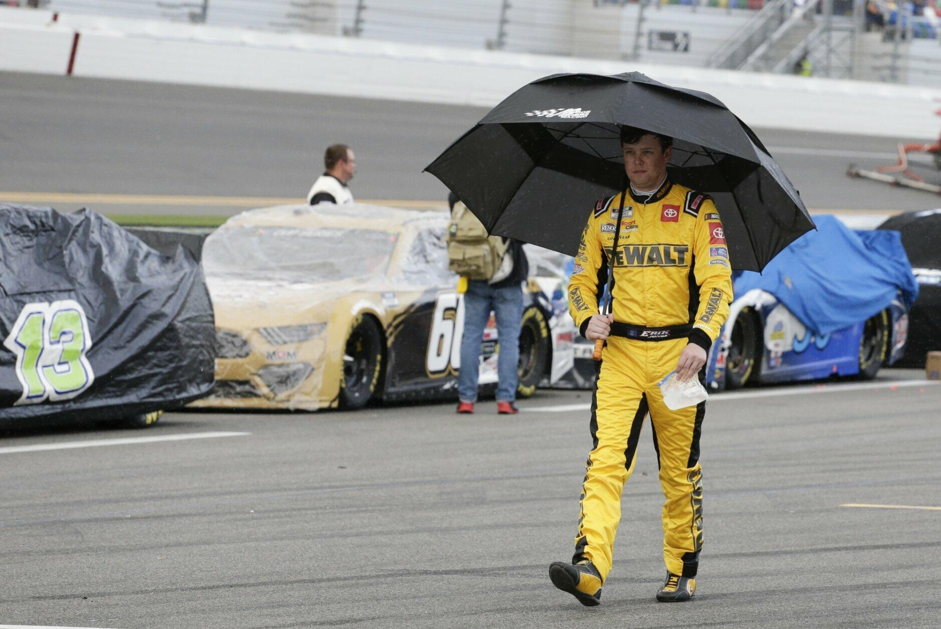 Erik Jones walks down pit road after rain caused a delay in the NASCAR Daytona 500 auto race at Daytona International Speedway, Sunday, Feb. 16, 2020, in Daytona Beach, Fla. (AP Photo/Terry Renna)