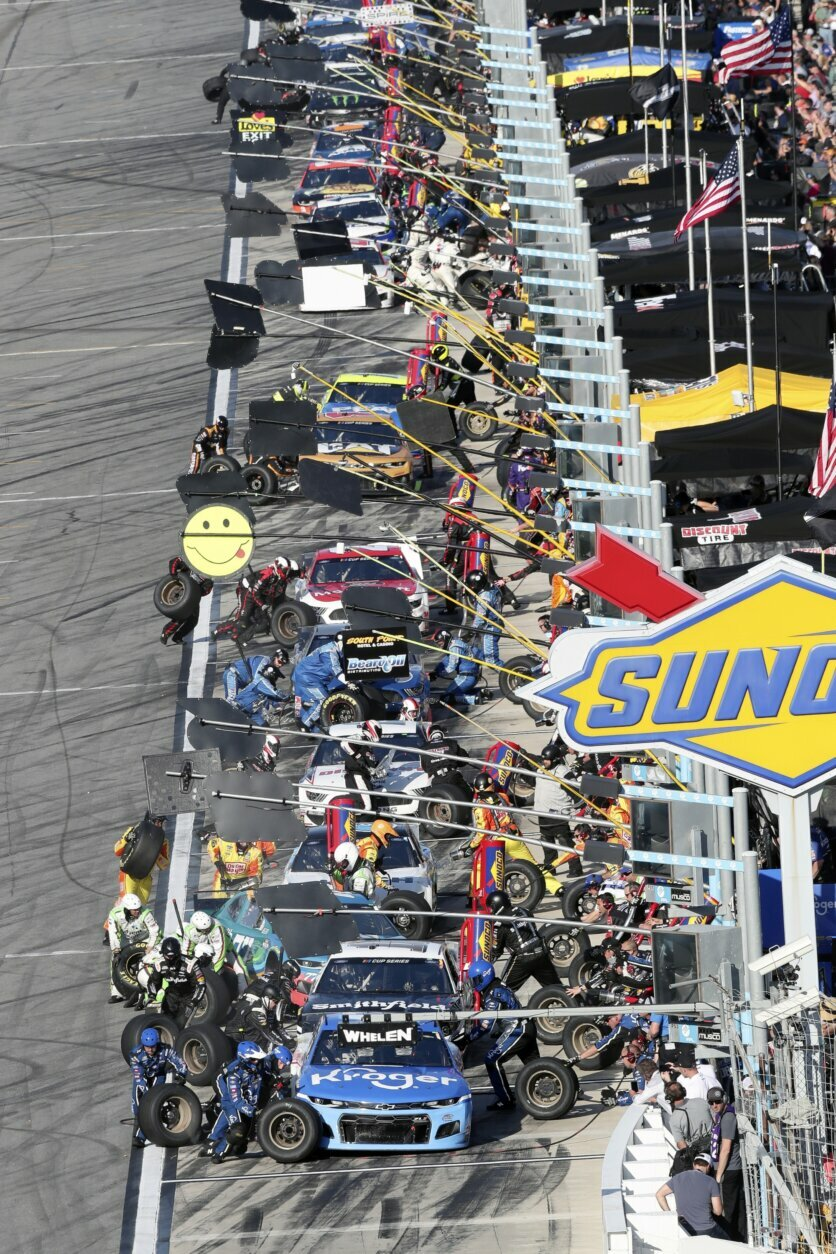 Ricky Stenhouse Jr., front, and the rest of the field come in for a pit stop during the NASCAR Daytona 500 auto race at Daytona International Speedway, Monday, Feb. 17, 2020, in Daytona Beach, Fla. Sunday's race was postponed due to rain. (AP Photo/David Graham)