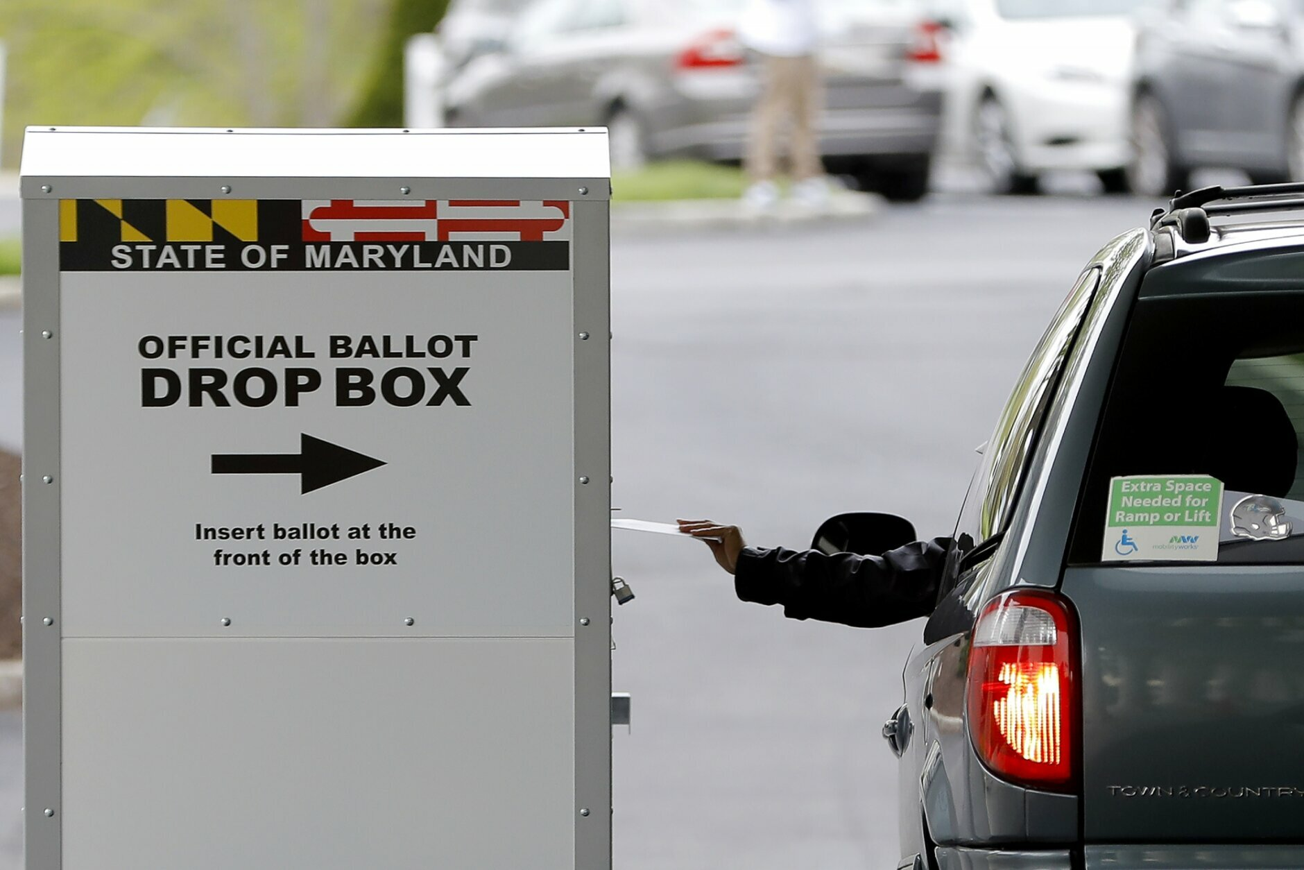 A motorist drops off a mail-in ballot outside of a voting center during the 7th Congressional District special election, Tuesday, April 28, 2020, in Windsor Mill, Md. The election to fill a seat left open by the death last October of Congressman Elijah Cummings has been dramatically reshaped by the coronavirus outbreak. (AP Photo/Julio Cortez)