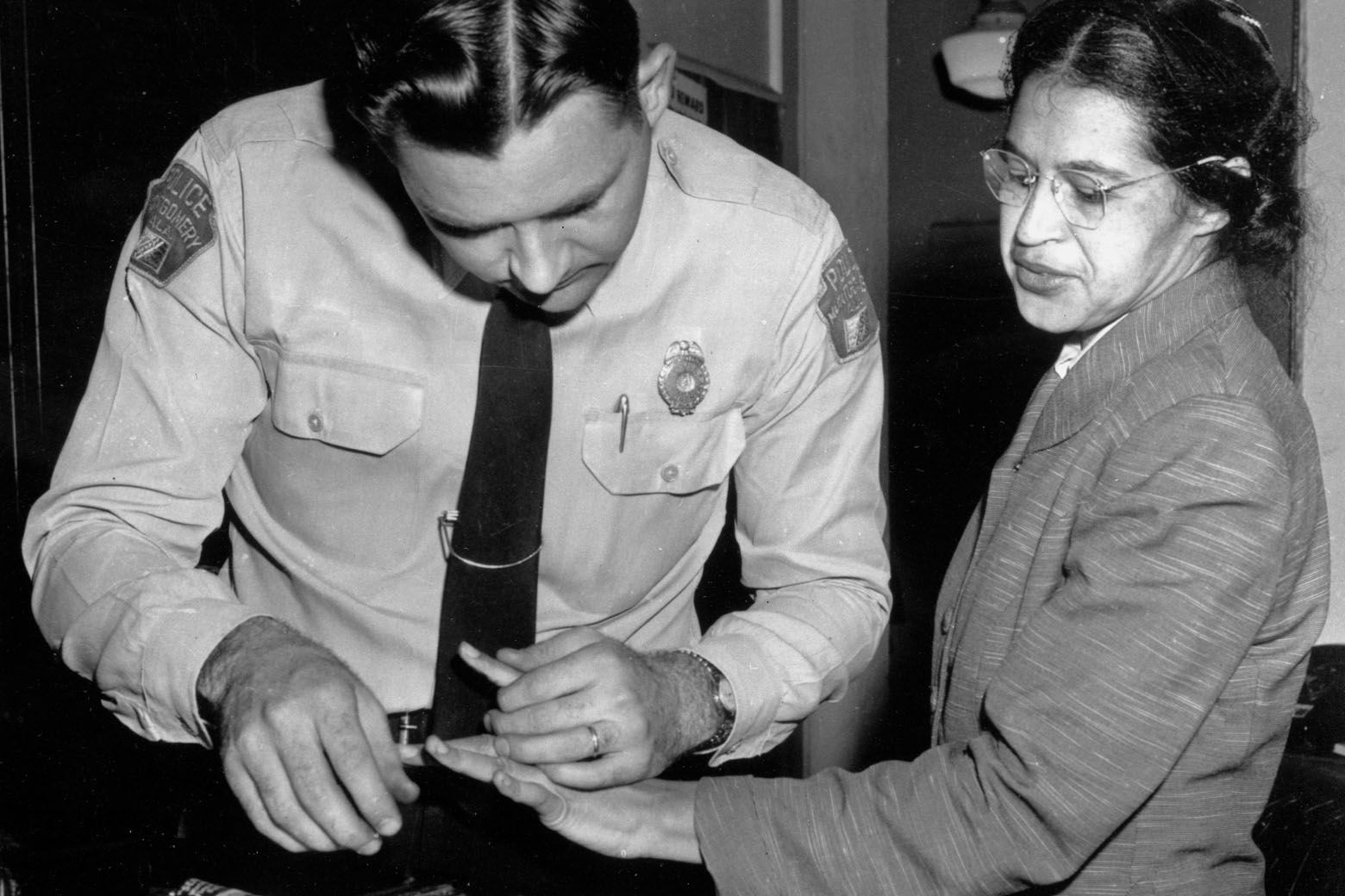 FILE - In this Feb. 22, 1956, file photo, Rosa Parks is fingerprinted by police Lt. D.H. Lackey in Montgomery, Ala., two months after refusing to give up her seat on a bus for a white passenger on Dec. 1, 1955. She was arrested with several others who violated segregation laws. Parks' refusal to give up her seat led to a boycott of buses by blacks in December 1955, a tactic organized by the Rev. Dr. Martin Luther King Jr., which ended after the U.S. Supreme Court deemed that all segregation was unlawful on Dec. 20, 1956. (AP Photo/Gene Herrick, File)