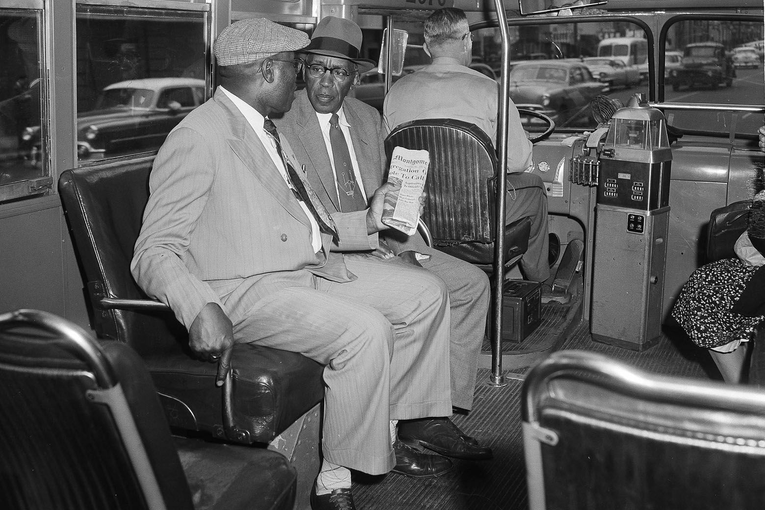 Two unidentified black men sit in the first seat behind the driver of a city bus in Montgomery, Al, Dec. 21, 1956, after the supreme court ruled racial segregation city on the buses as unconstitutional.  The federal court order ended the Montgomery bus boycott, which lasted 381 days.  (AP Photo)