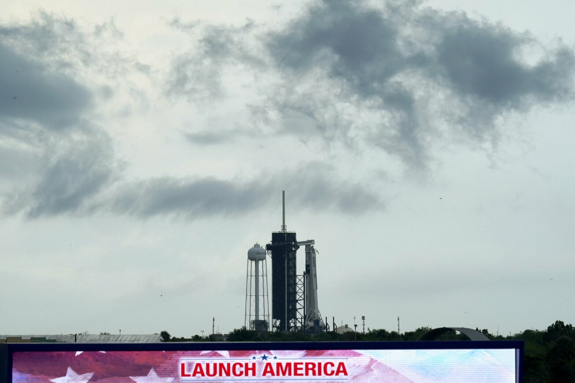 Clouds pass over the SpaceX Falcon 9, with the Crew Dragon spacecraft on top of the rocket, as it sits on Launch Pad 39-A Wednesday, May 27, 2020, at Kennedy Space Center in Cape Canaveral, Fla. Two astronauts will fly on the SpaceX Demo-2 mission to the International Space Station scheduled for launch Wednesday. (AP Photo/David J. Phillip)