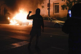 <p>A demonstrator is filmed in front of a burning car during a protest of the death of George Floyd, Sunday, May 31, 2020, near the White House in Washington. Floyd died after being restrained by Minneapolis police officers. (AP Photo/Evan Vucci)</p>