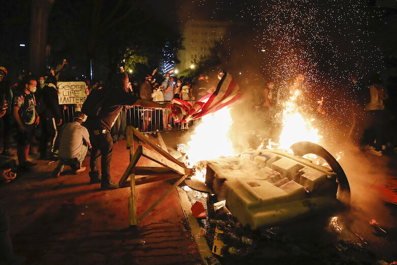 <p>Demonstrators start a fire as they protest the death of George Floyd, Sunday, May 31, 2020, near the White House in Washington. Floyd died after being restrained by Minneapolis police officers (AP Photo/Alex Brandon)</p>