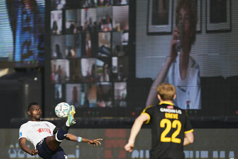 AARHUS, DENMARK - MAY 28: Mustapha Bundu of AGF Aarhus in action in front of the LED screens with fans following the game via zoom during the Danish 3F Superliga match between AGF Aarhus and Randers FC at Ceres Park on May 28, 2020 in Aarhus, Denmark. (Photo by Lars Ronbog / FrontZoneSport via Getty Images)