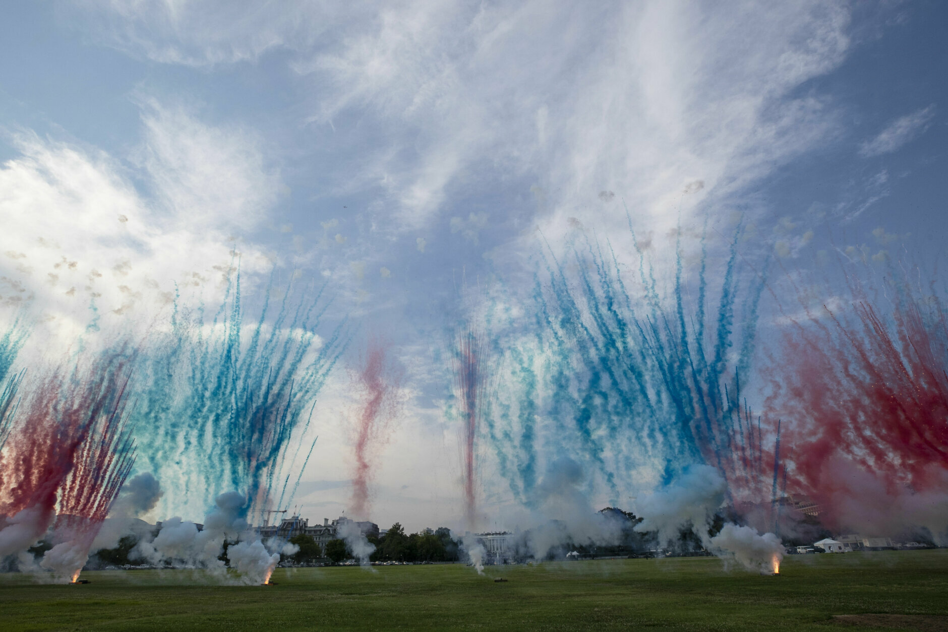 """The White House, center, is obscured by Red and Blue smoke from fireworks on the Ellipse during a """"Salute to America"""" event on the South Lawn of the White House, Saturday, July 4, 2020, in Washington. (AP Photo/Alex Brandon)"""