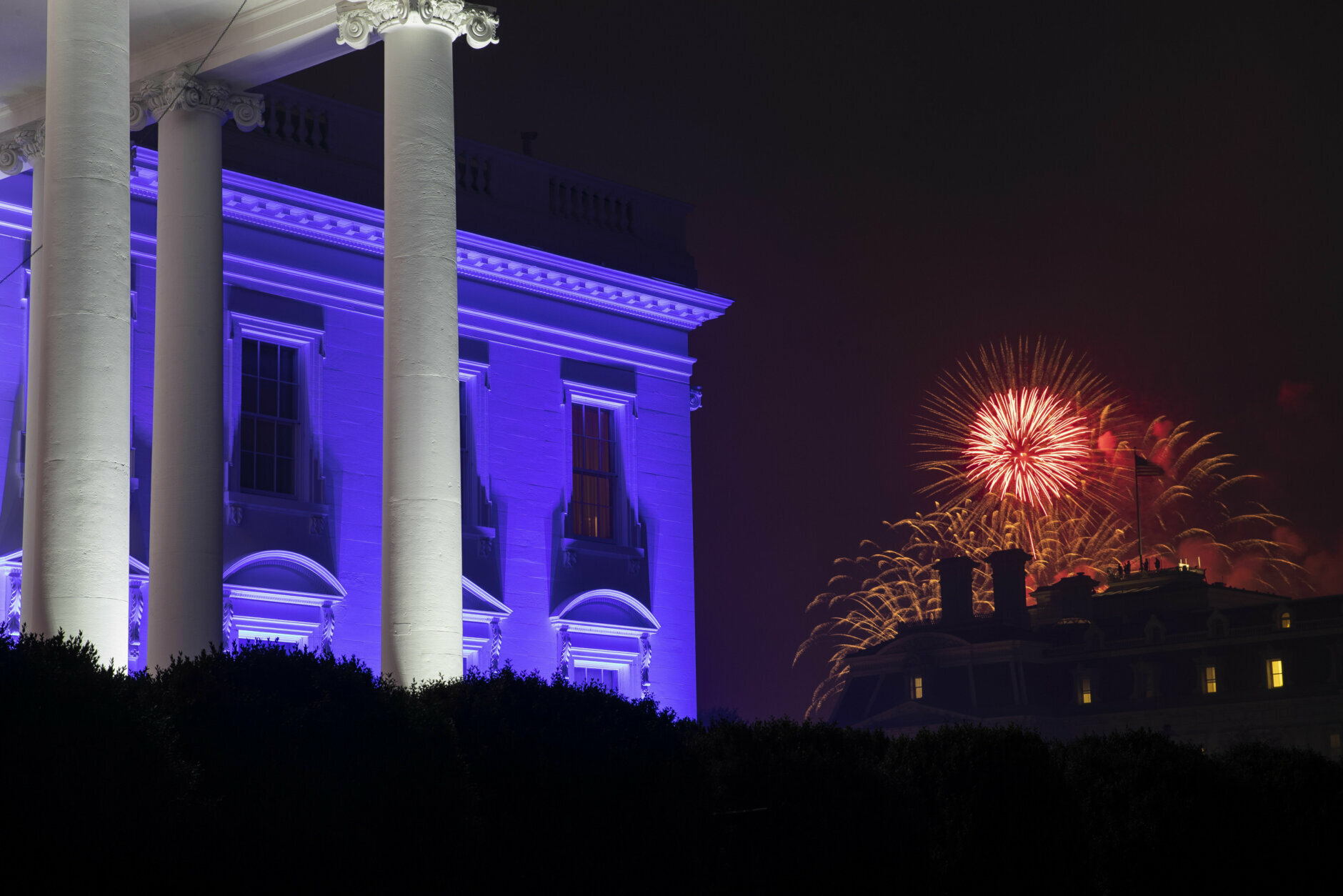 """The White House is illuminated with red, white and blue lights as fireworks burst in the distance during a """"Salute to America"""" event Saturday, July 4, 2020, in Washington. (AP Photo/Alex Brandon)"""