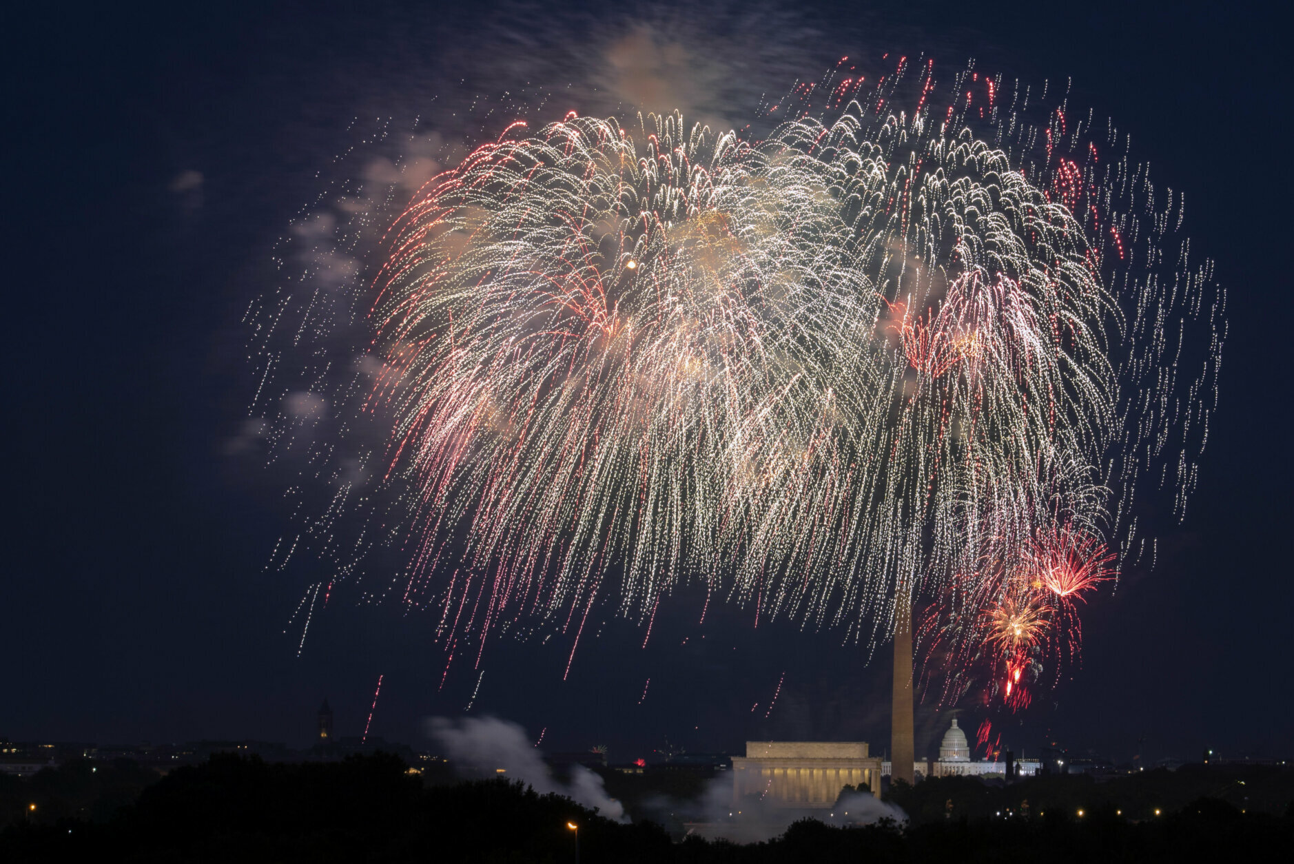 Fourth of July fireworks explode over the Lincoln Memorial, the Washington Monument and the U.S. Capitol along the National Mall in Washington, Saturday, July 4, 2020. (AP Photo/Cliff Owen)