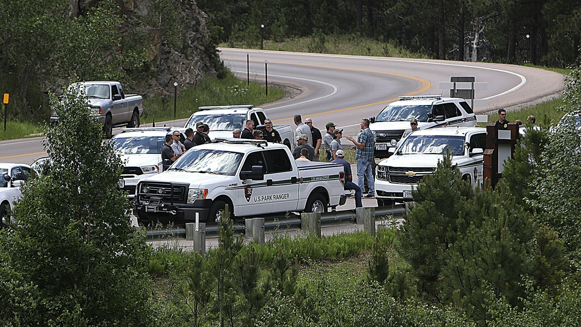 Law enforcement officers meet Thursday, July 2, 2020, at the site near Horse Thief Lake where traffic trying to enter the Mount Rushmore National Memorial, S.D., will be stopped and screened. Ticket holders to the fireworks display Friday at Mount Rushmore will be allowed to continue along Highway 244. Those without tickets will be told to turn around. President Donald Trump is scheduled to visit Mount Rushmore on Friday. (Jeff Easton/Rapid City Journal via AP)