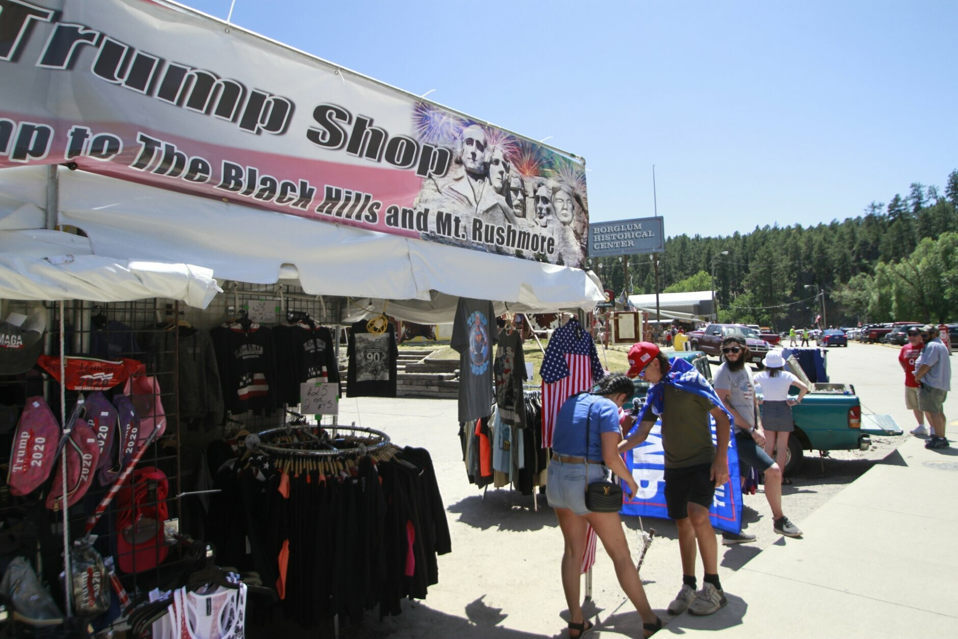 People shop for Trump memorabilia in Keystone, S.D. on Friday, July 3, 2020 ahead of a fireworks display at Mount Rushmore the president is expected to attend. (AP Photo/Stephen Groves)
